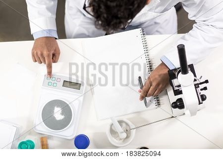 Overhead View Of Young Scientist Working With Electronic Scales And Taking Notes In Research Laborat
