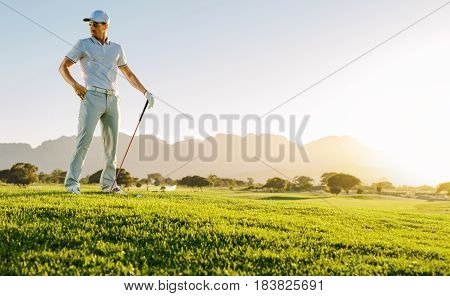 Young Man With Golf Stick On Field