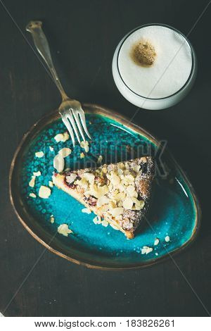 Dessert and coffee. Piece of lemon, ricotta, almond and raspberry gluten-free cake and glass of latte over dark wooden background, top view