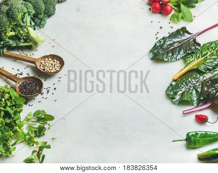 Fresh raw greens, unprocessed vegetables and grains over light grey marble kitchen countertop, copy space. Clean eating, healthy, vegan, vegetarian, detox, dieting food concept