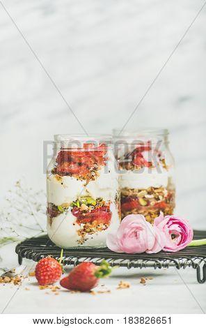Healthy spring breakfast. Greek yogurt, granola, fresh strawberry breakfast in jars, pink raninkulus flowers, marble background, selective focus, copy space. Clean eating, vegetarian food concept