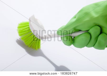 Hand in Rubber Glove Holding a Brush on the Grey Background