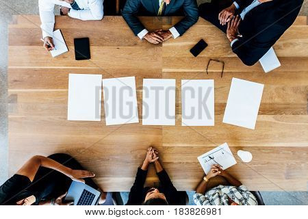 Top view of office workers sitting around a table in conference room. Multi-ethnic business people in meeting with blank pages on table.