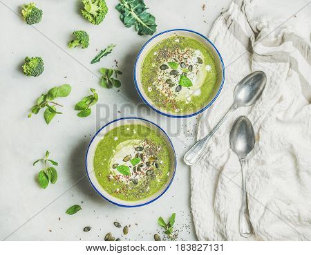Spring detox broccoli green cream soup with mint and coconut cream in bowls over light grey marble background, top view. Clean eating, dieting, vegan, vegetarian, healthy food concept