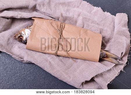 dried fish roach wrapped in brown craft paper on a black surface
