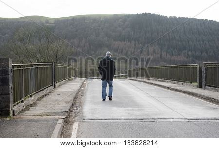 Rear view of a mature man walking along a quiet road in winter