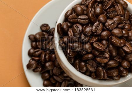Coffee cup and saucer filled with coffee beans