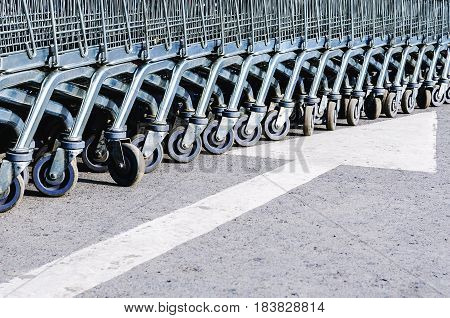 View of a Row of Stacked Supermarket Trolleys Close-up on the asphalt with a road marking arrow