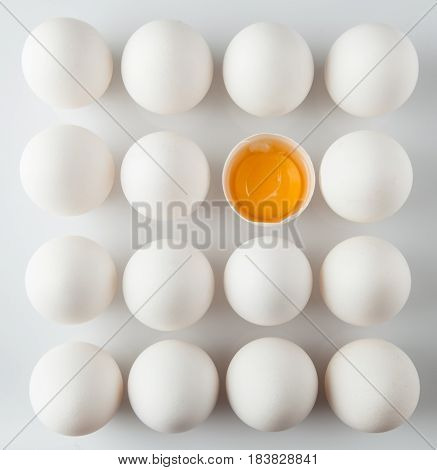 Single Cracked Egg Amongst Many Intact Eggs Top-down View