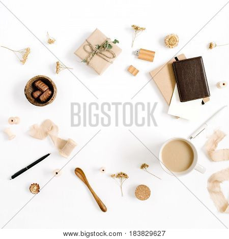 Blogger or freelancer workspace with coffee mug, notebook, sweets and accessories on white background. Flat lay, top view minimalistic brown styled home office desk. Brown styled composition