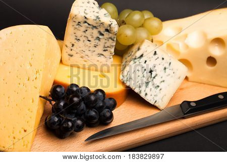 Knife, Cheese and Grape on the Wooden Platter on Black Background