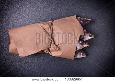 withered in salt and dried fish roach wrapped in brown kraft paper close up