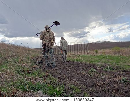 Two men walking through the meadow with metal detectors and shovels in their hands