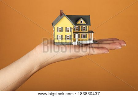 Women's Hand Holding a Model of a House on Orange Background