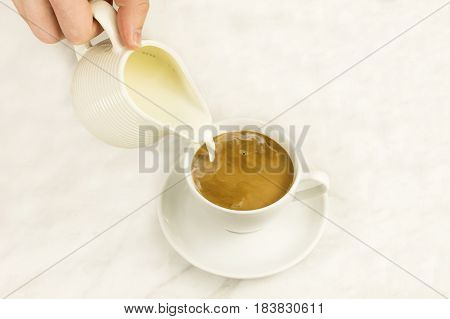 Milk poured into a cup of coffee, on a white marble background with a place for text