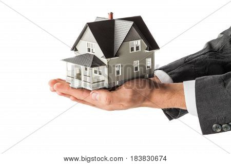Men's Cupped Hands Holding a Model of a House