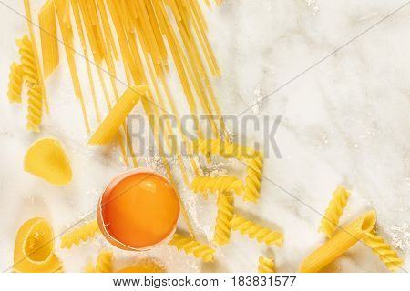 An egg and pasta with traces of flour, shot from above on a white marble texture with a place for text