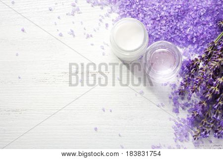 Sprigs of lavender,  mineral bath salts, jars with shower gel  and cream on the wooden table.