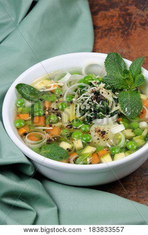 Light refreshing soup of carrots zucchini potatoes leeks peas pesto parmesan and mint leaves.