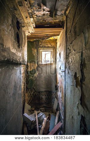 Room in abandoned house, Light from a small window, craggy walls, debris, toilet bowl, vertical image