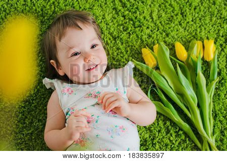 The child lies on the grass and is happy with a bouquet of yellow tulips