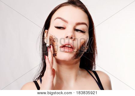 beauty people and healthy skin concept - Brunette cleanses skin coffee scrub white background Beauty Portrait. Beautiful Spa Woman Touching her Face. Perfect Fresh Skin Youth and Skin Care Concept