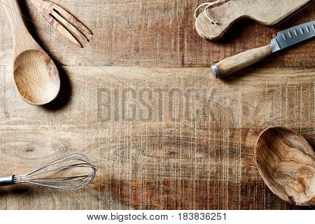 Assorted wooden kitchen utensils on a rustic wooden surface