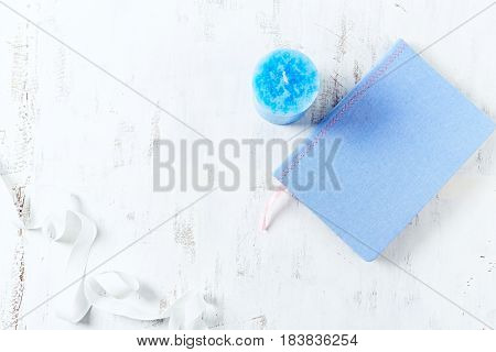 Desk workspace with blue notebook and a candle. Flat lay composition