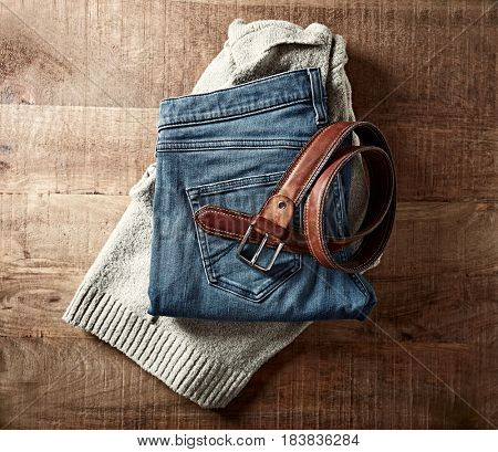 Casual  woman clothes and belt on wooden surface