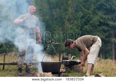 Man Cooking Meat Over Bonfire At Campsite