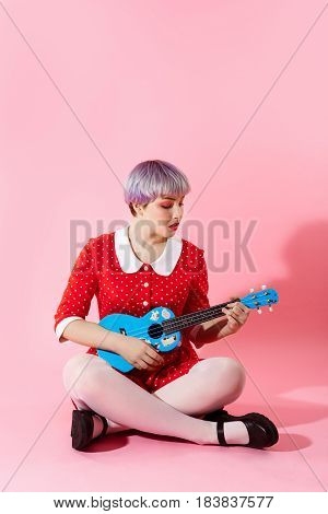 Picture of beautiful dollish girl with short light violet hair wearing red dress playing blue ukulele over pink background. Copy space.