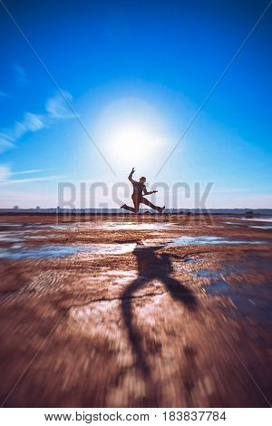 Handsome man jumping with guitar on sunset or sunrise outdoors