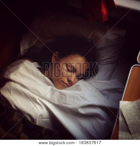 Young beautiful woman sleeping under the white Bed sheets