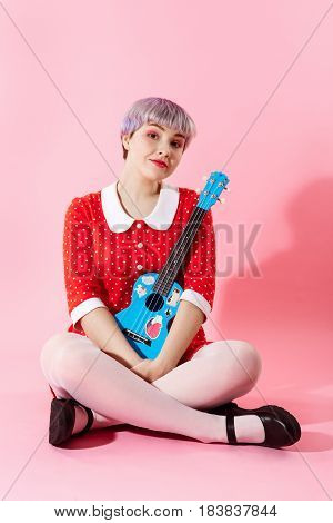 Picture of beautiful dollish girl with short light violet hair wearing red dress holding blue ukulele over pink background. Copy space.
