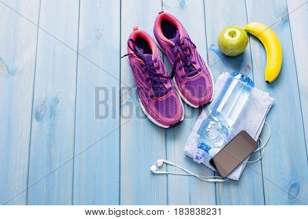 fitness healthy concept shoes applewater and smart phone on wooden background