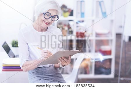 Let me think. Delighted female bowing her head holding folder in left hand while keeping smile on her face