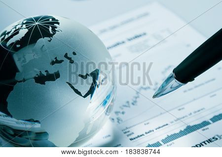 Glass Globe And Pen On Financial Report Close-up