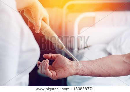 doctor with the phone treats a patient with a skin disease using the Darsonval apparatus for the treatment of dermatitis apathic seborrhea eczema..high contrast