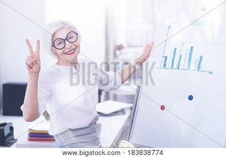Glad to work here. Joyful office worker keeping smile on her face putting left hand on the board while showing victory sign