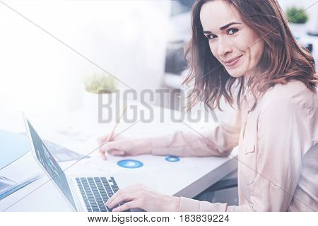 Love my job. Shy female sitting in semi position turning her head to camera, holding pencil in right hand while touching her keyboard