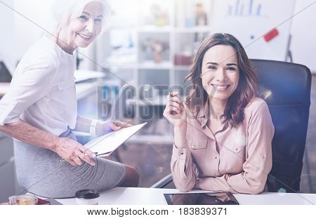 Make a shot. Positive brunette putting her arms on the table keeping pen in right hand while looking forward