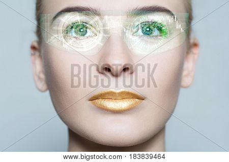 Young woman looking with futuristic smart glasses. Beautiful and attractive girl with gold make-up from future in process of scanning. Virtual hologram on her high tech glasses