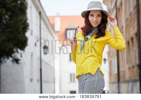 Outdoor fashion portrait of pretty stylish laughing woman in grey wool hat.Yellow jacket, overall , bright make up, European street background. Street look. Enjoy weekends.