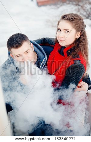vape Closeup of a loving girl and boyfriend smokes an e-cigarette on a sunset background.steam is falling. Concept rejection of cigarettes. vaping