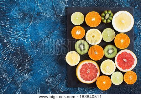 Fruits rich in vitamin C: oranges lemons kiwis grapefruits and limes on the black slate on the dark blue background top view