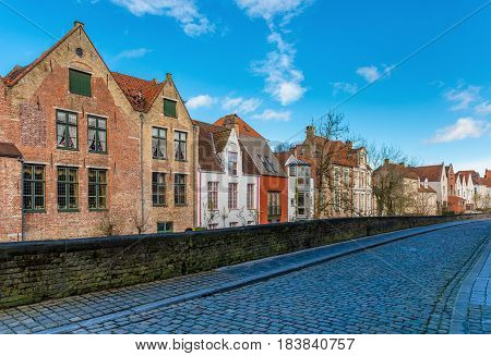 Bruges (Brugge) - February of 2016, Belgium: Typical belgian street with traditional varicolored houses and stone road