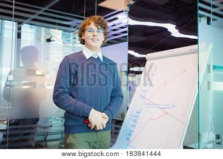 Handsome teenager in glasses stands near graphs on paper in modern office