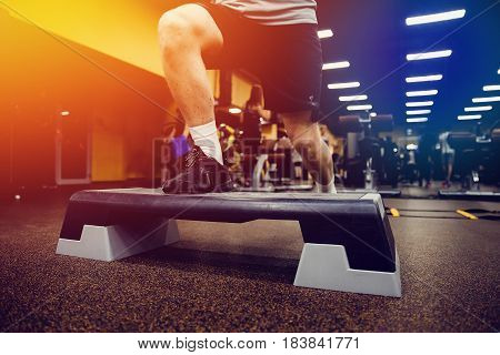 Close-up man Step for exercises in the gym with an athlete's foot.high contrast and monochrome color tone. Weight Loss. Strength of will. Psychological struggle.