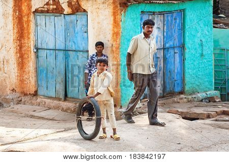 BADAMI, INDIA - FEB 10, 2017: Unidentified boy playing on the narrow street with rushing people and rustic houses on February 10, 2017. Population of Karnataka state is 62000000 people