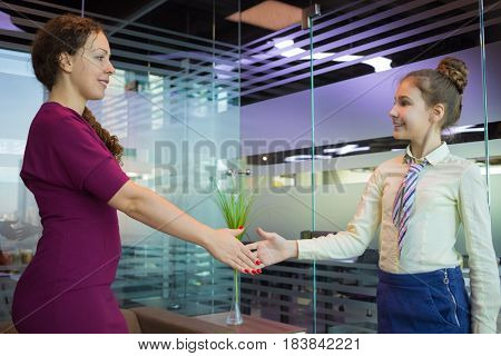 Woman and girl in tie handshake in modern office with glass walls